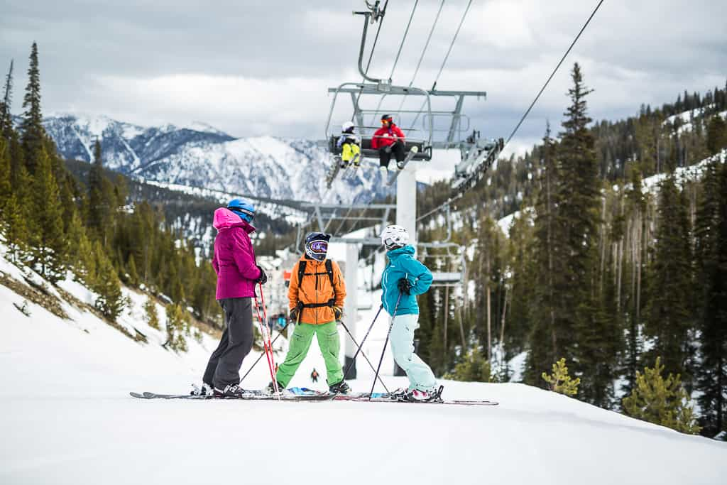 Family of skiers take a quick break under the chairlift at Big Sky