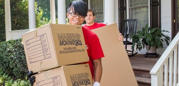 two movers carrying marrins' moving boxes