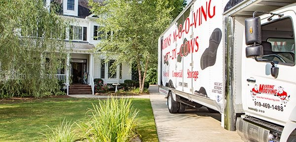 Marrin's Moving truck backed into a driveway of a large white house, preparing for a move