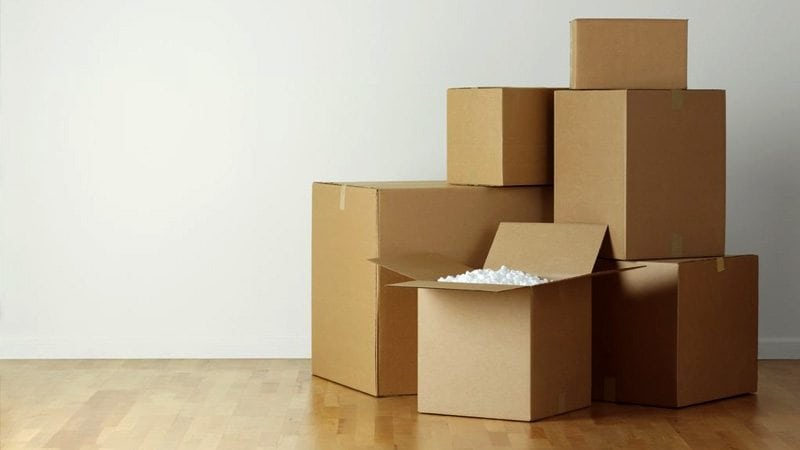 Cardboard moving boxes stacked on a wooden floor, with one open and styrofoam packaging visible.