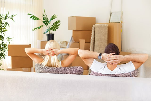 A couple relaxing wth their hands behind their head as professionals take care of a move with white glove service
