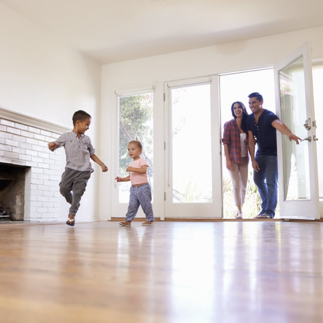 A young family of four excitedly moving into a brand new house with bare floors and walls