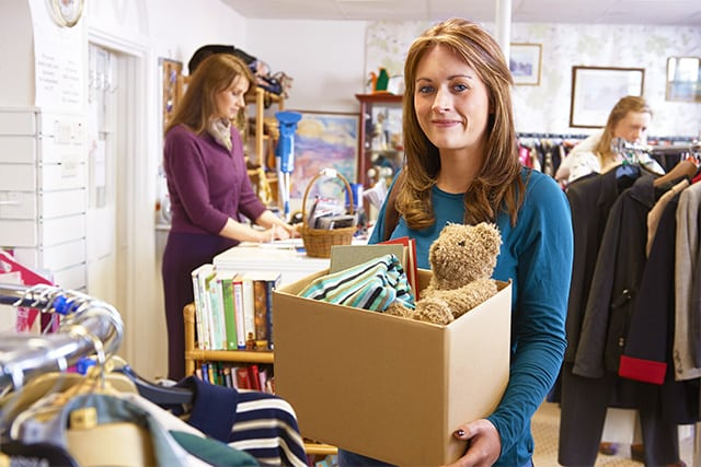 Woman holding a cardboard box of books, clothes, and a stuffed teddy bear preparing to give away at a donation center.