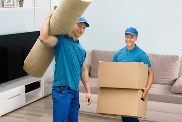 Two professional movers, one holding two boxes and another carrying a rug, smiling and preparing to move out