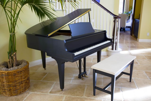 Black grand piano in front of a staircase next to a potted plant.