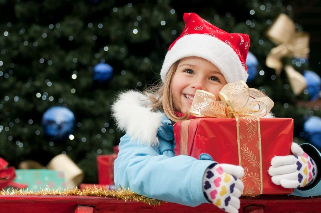 Young girl wearing a Santa cap smiling and holding a red package with a bow