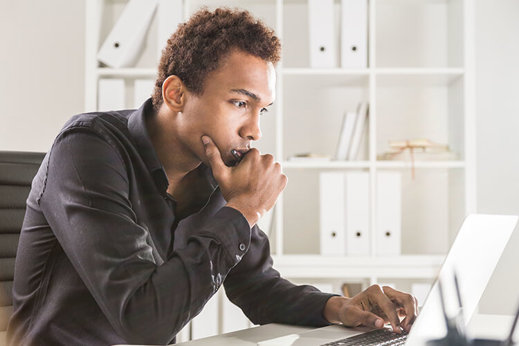 man looking at computer screen and thinking