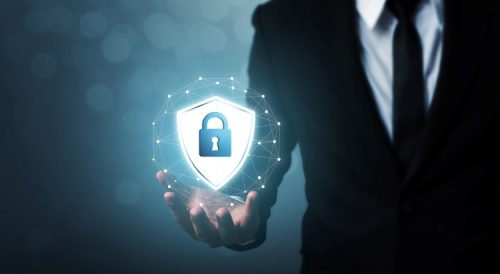 A cyber security professional in a suit holds a digital image of a lock icon