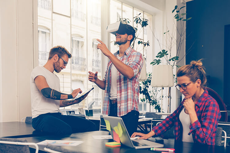 man uses VR headset in office with coworkers