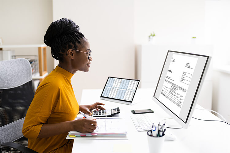 a managerial accountant reviews sits at desk to review an invoice