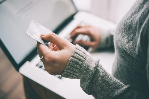 woman holds credit card while typing on laptop