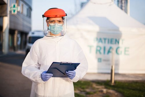 nurse in PPE with clipboard standing outside