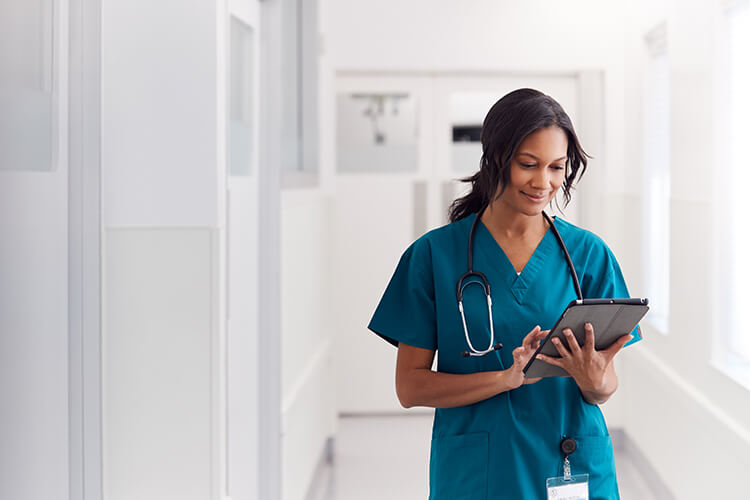 Nurse in hospital hall using a digital tablet