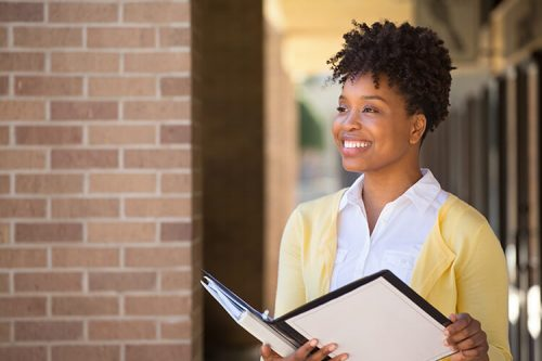 woman smiles outside building while holding binder