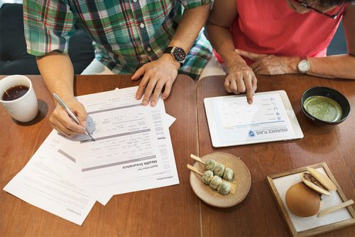 couple filling out insurance forms at a table