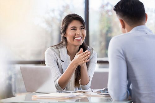 Woman listening and conversing at conference room table