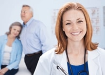 Nurse Practitioner smiling in camera with two patients in the background