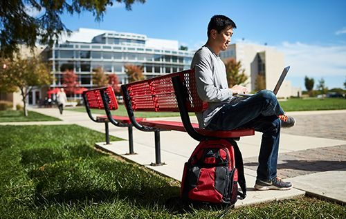 Student sitting on bench attending Maryville University
