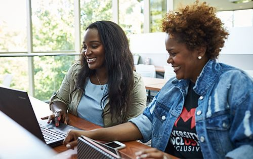 Two female students looking at laptop