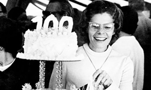 Centennial Timeline - Woman enjoying birthday cake with 100 candle