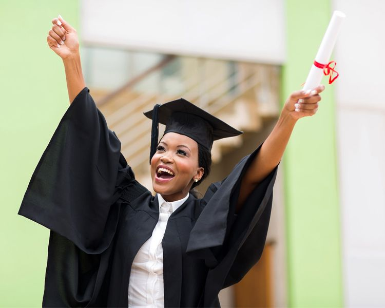 Female graduate in cap and gown holding diploma in air
