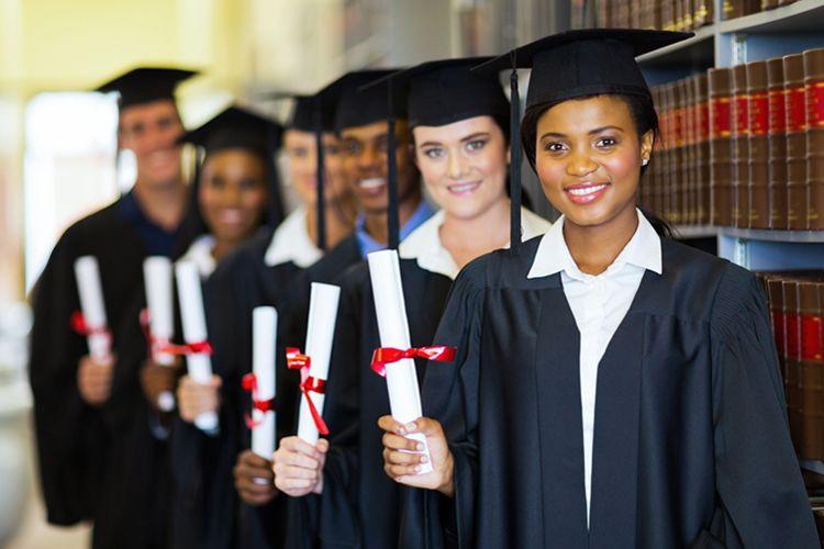 Smiling graduates holding diplomas