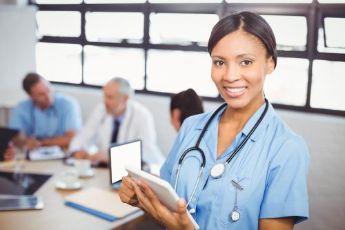 nurse practitioner with tablet dressed in blue scrubs