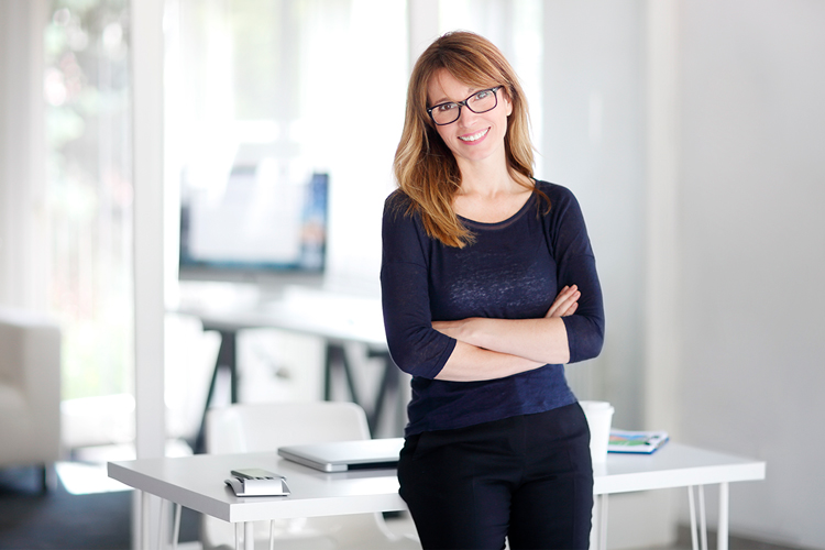 smiling women manager with arms crossed learning against desk