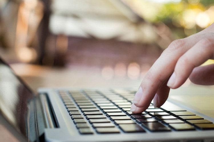 hand typing on laptop