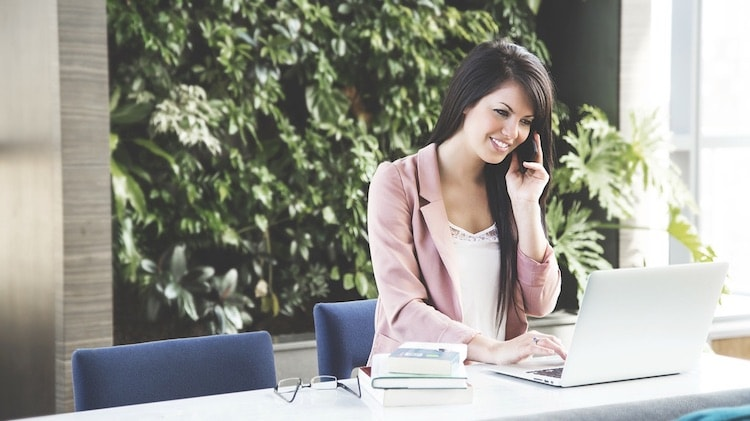 Female accounting student on phone at desk