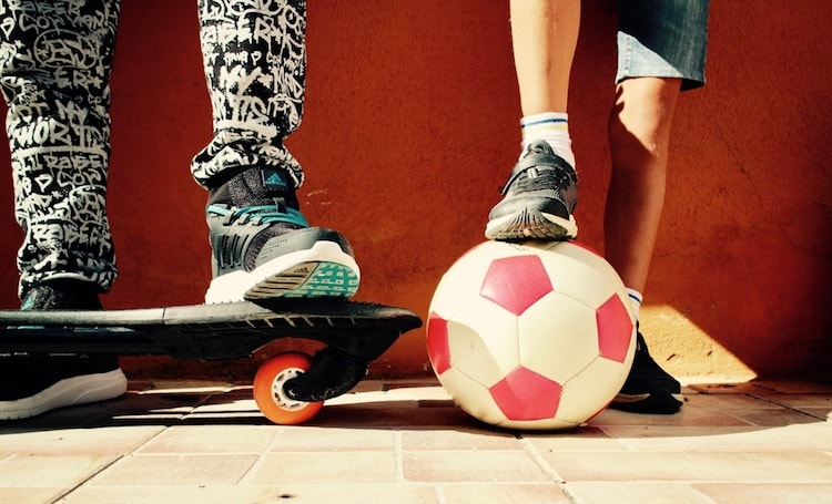 kids with feet propped up on skateboard and soccer ball