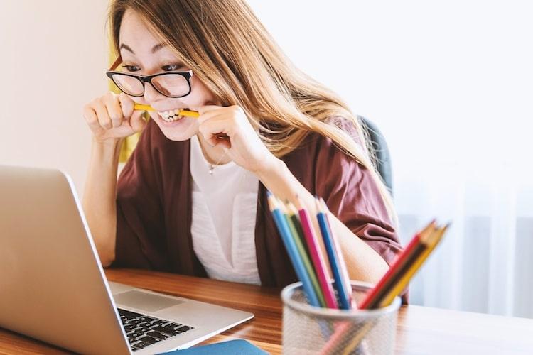 Writer biting pencil while looking nervously at laptop