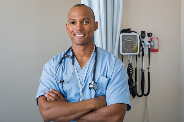 smiling male nursing student with crossed arms