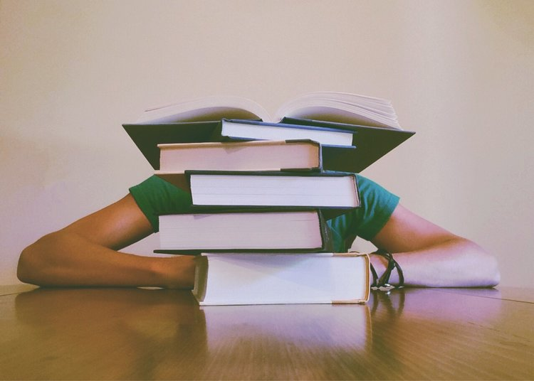 Student hidden behind pile of books