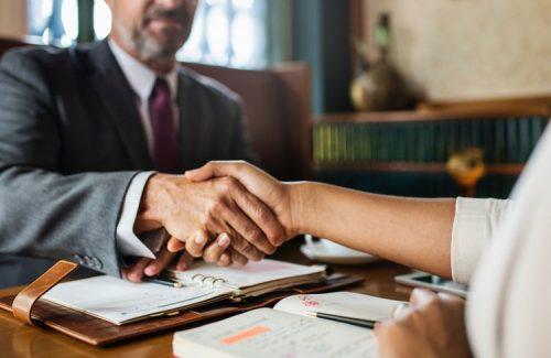 College graduate shaking hands over a desk