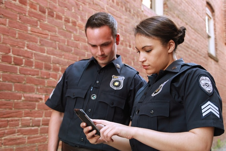 Two police officers looking at a smartphone