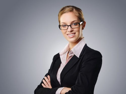 Lady wearing suit with arms crossed smiling