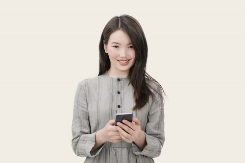 Lady holding a cell phone smiling straight forward
