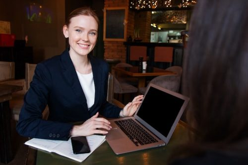 Female profesional sitting down with laptop and phone on desk
