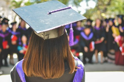 A graduate student in cap and gown at her commencement ceremony
