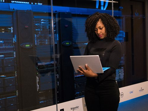 Lady using a laptop while standing in data center