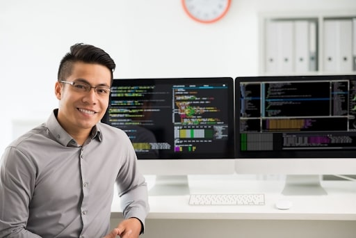 Male professional smiling while sitting in front of two computer monitors