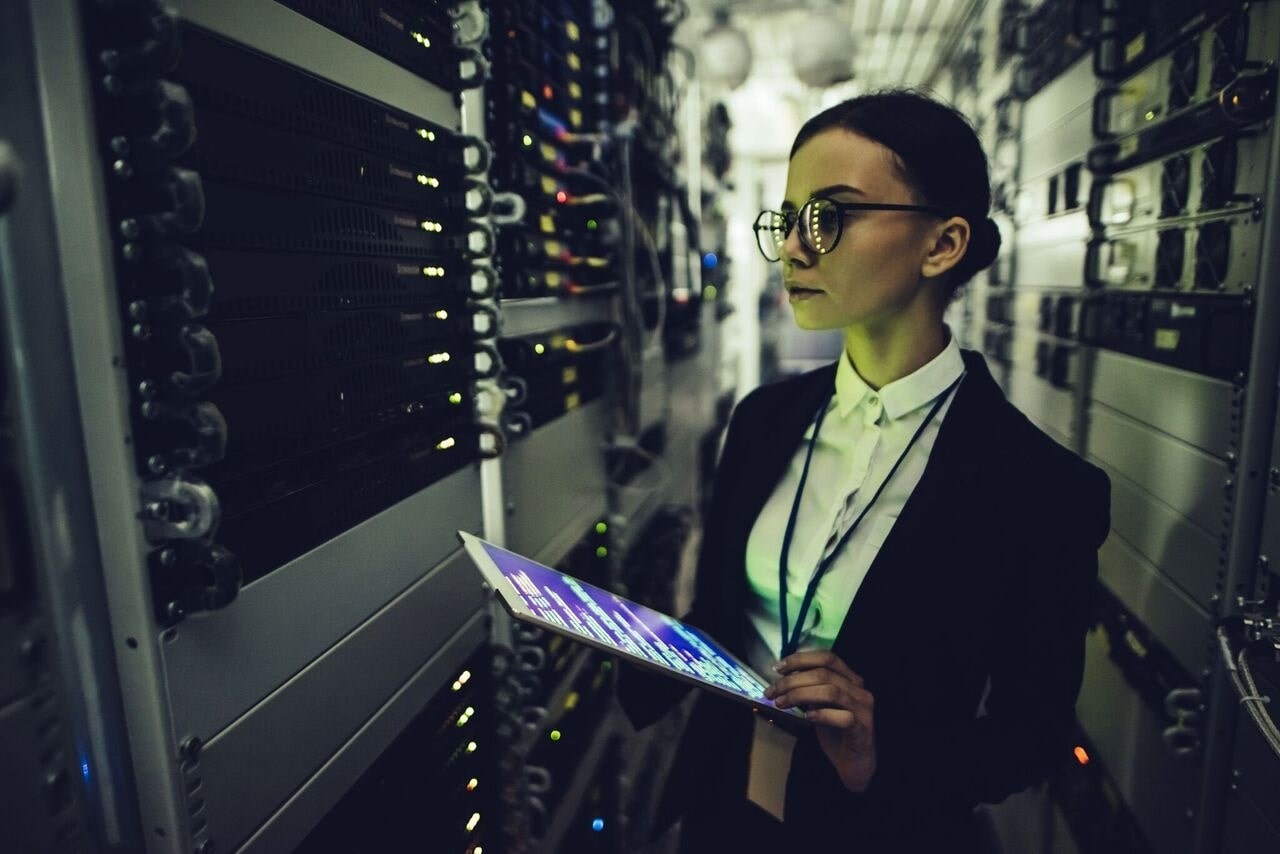 Woman holding a tablet looking at servers in a data center