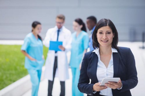a female professional standing in front of a group of healthcare professionals