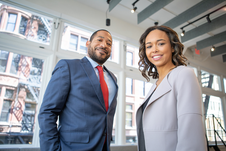 A man and woman wearing suits while smiling