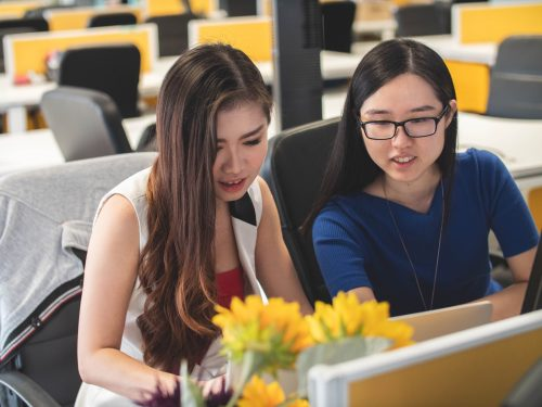 shallow focus photography of two women doing work at a table