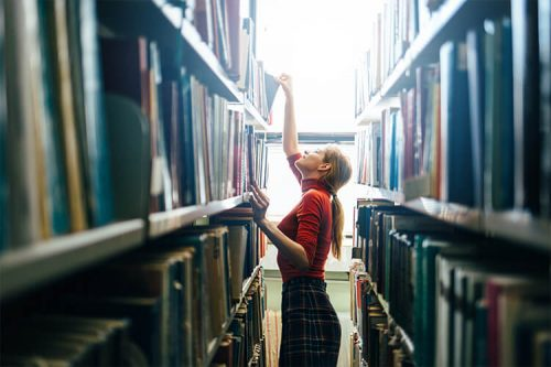 A young, female college student looking for a book on the shelves at her school library.