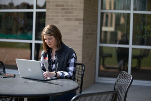 student sitting outdoors on her computer