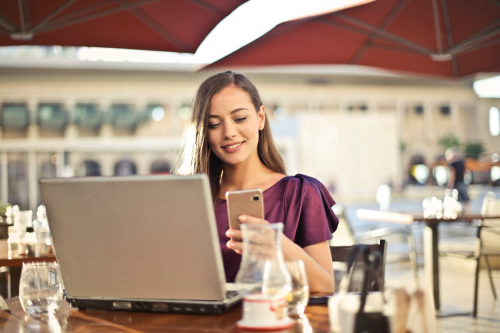 A smiling woman in a purple blouse, in an outdoor cafe, checks both her phone and laptop.