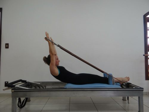 A woman uses physical therapy equipment to do a Pilates exercise.